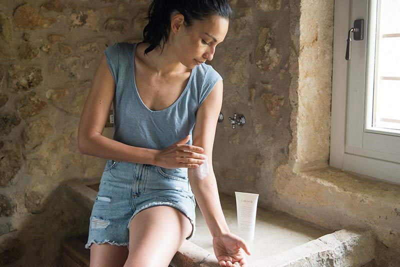 Ragazza applica all'interno del gomito la Crema Grassa per Dermatite Atopica di Laevia