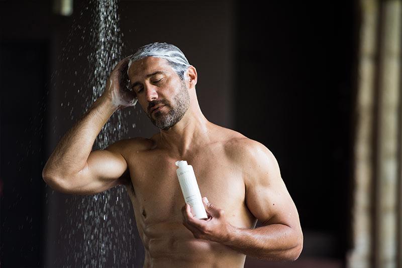 Uomo lava i capelli con lo shampoo delicato per dermatite seborroica Laevia