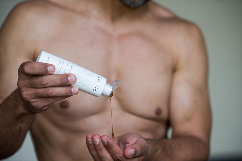 Uomo versa sulla mano lo shampoo delicato per dermatite seborroica Laevia